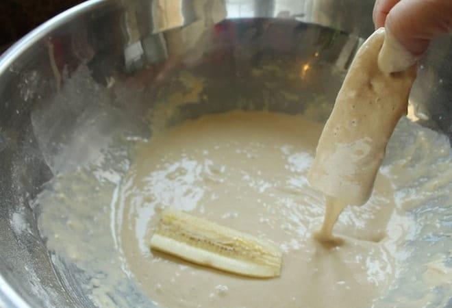 Для приготовления жареных бананов, следуя рецепту с фото пошагово, обмакиваем заготовки в кляр