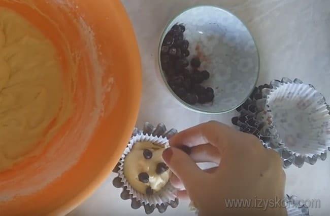 Каждый маффин, приготовленный по рецепту со сметаной, посыпаем ягодами перед отправкой в духовку.