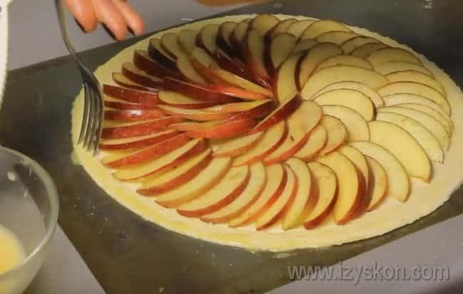 Надо наколоть тесто вилкой по краю, чтобы оно не вздымалось и не портило вид открытого яблочного пирога.