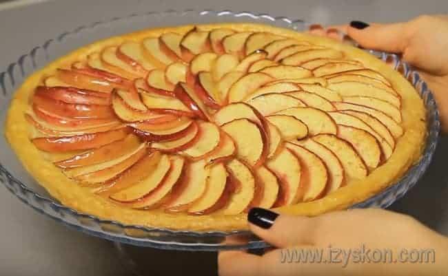 Выпекается такой открытый яблочный пирог около часа.