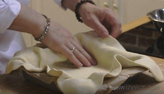 Тесто для пирога с капустой и рыбой выкладываем в форму так, чтобы края немного заходили за бортики.