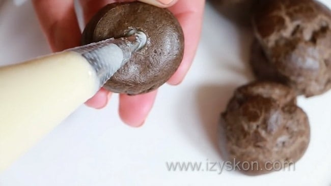 Наполните шоколадные профитроли кремом.
