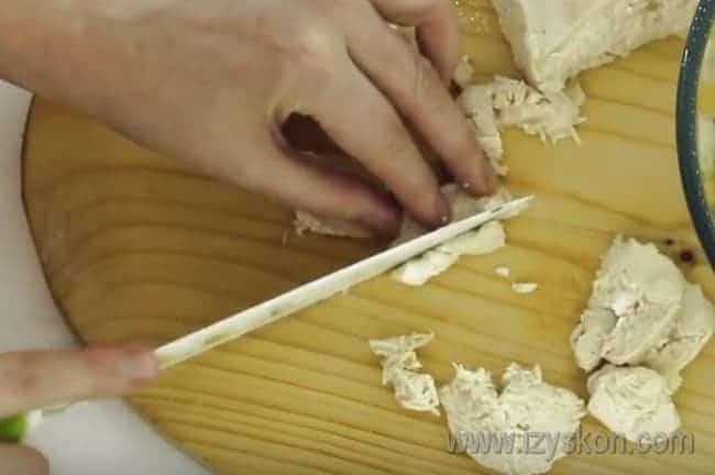 нарежьте небольшими кусочками куриное филе для приготовления салата из пекинской капусты с кукурузой.