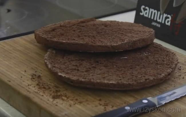 Корж для приготовления торта Сникерс с безе и орехами разрезаем на две одинаковые части.