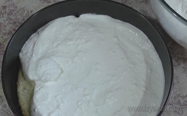 Собираем наш желейно-бисквитный торт с фруктами: пропитанный бисквит заливаем сметаной.