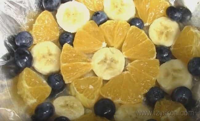 Для приготовления простого желейного торта с фруктами и сметаной на дно миски или формы выкладываем фрукты и заливаем из сметанной смесью.