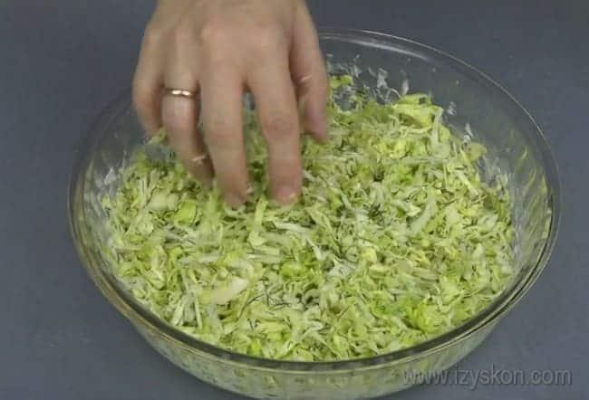 Вылив половину теста для заливного пирога с капустой на сметане, выкладываем на него начинку.