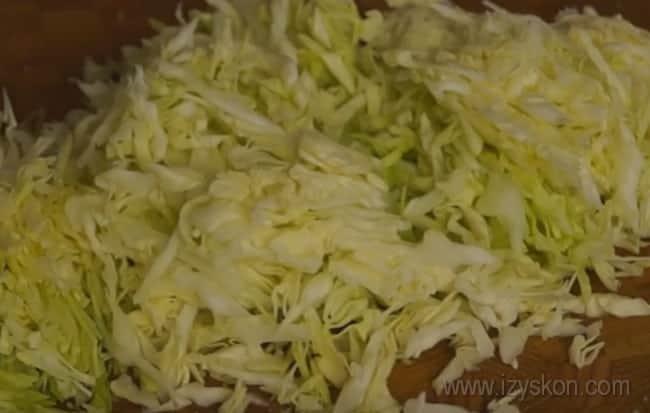 Мелко нашинкуйте капусту для заливного пирога с мясом и капустой.