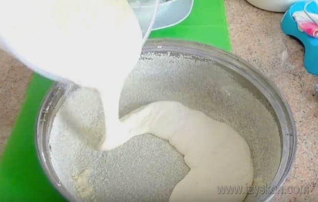 В форму выливаем половину теста для нашего заливного пирога с консервированной рыбой.