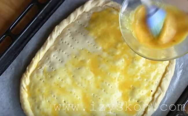 Для румяности смазываем пирог взбитым яйцом с куркумой.