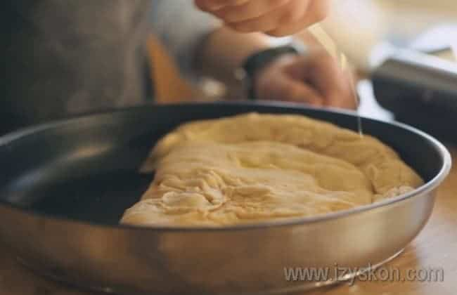 Перекладываем пиццу на противень или форму для выпечки, сбрызгиваем оливковым маслом и посыпаем орегано.