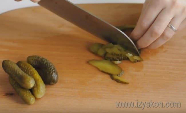 Нарезаем огурцы для того, чтобы приготовить вкусную сборную мясную солянку.