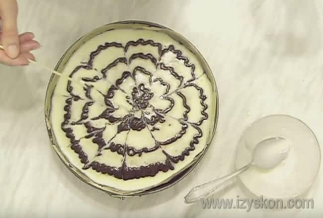 Оформляем пирог пр помощи растопленного шоколада, делая узоры зубочисткой.