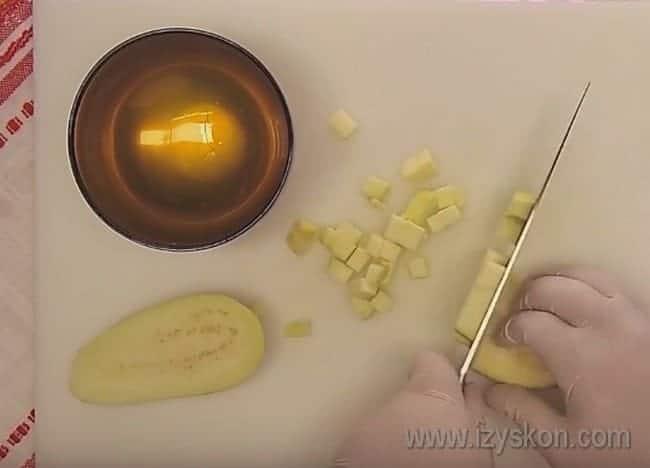 Очистив от кожуры баклажан, тоже режем его кубиками.
