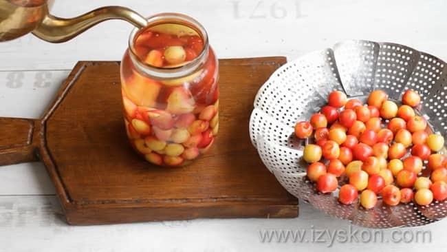 Для приготовления компота из черешни с косточками на зиму залейте ягоды кипятком.