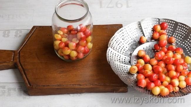 Для приготовления компота из черешни с косточками на зиму уложите ягоды в банку.