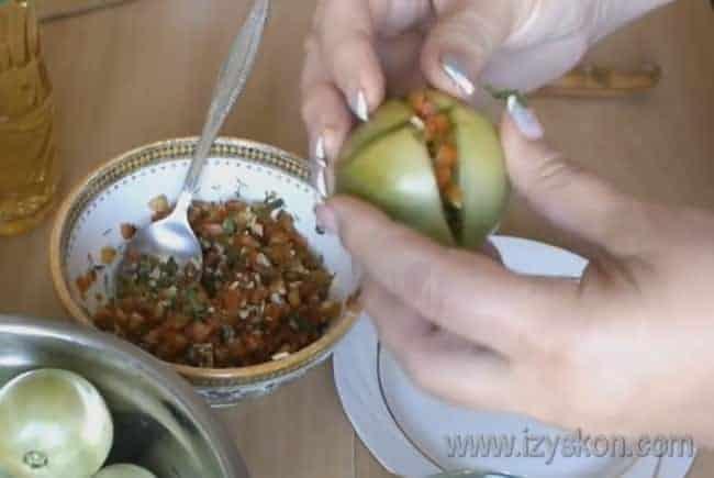 Фаршируем помидоры приготовленной начинкой и плотно укладываем в банки.