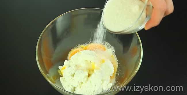 В миску с желтками добавляем творог и сахар