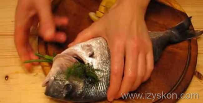 Внутрь рыбы кладем веточку укропа и лимон