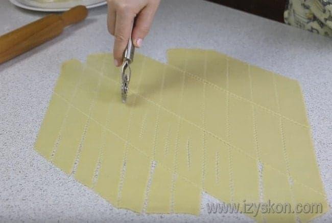 Разрезаем тесто на полоски, по центру каждой делаем небольшое отверстие.