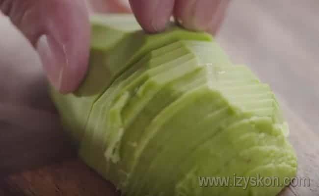 Чтобы приготовить брускетту с авокадо, нарезаем его тоненькими ломтиками. предварительно очистив от кожуры и вынув косточку.