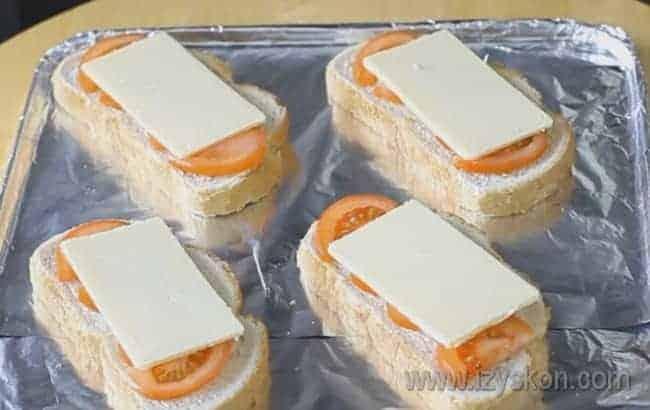 Помидор покрываем ломтиками сыра.