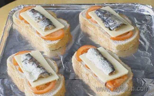 Поверх сыра выкладываем шпроты.