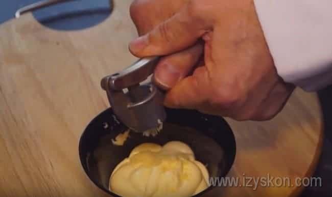 Чтобы сделать ароматные горячи бутерброды в духовке, выдавливаем чеснок в майонез.
