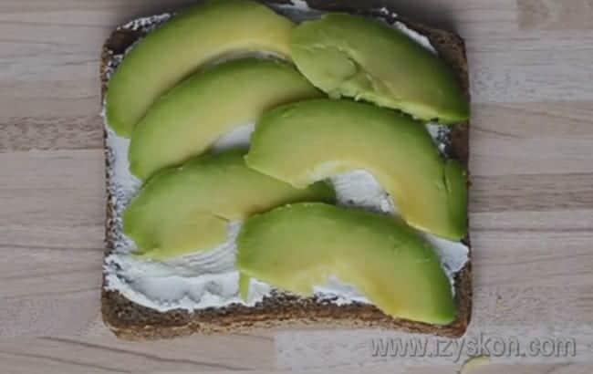 Намазав хлеб сыром, выкладываем на него тонкие ломтики авокадо.