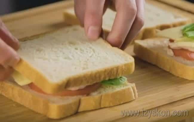 Поверх сыра выкладываем салат и накрываем его еще одним ломтиком хлеба.