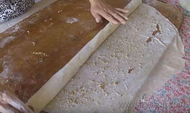 При помощи скалки сворачиваем тесто в рулет.