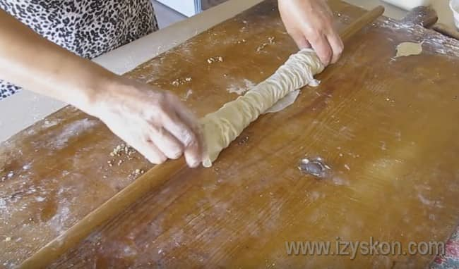 Прямо на скалке по бокам сжимаем тесто, чтобы наш рулет уменьшился в размерах.