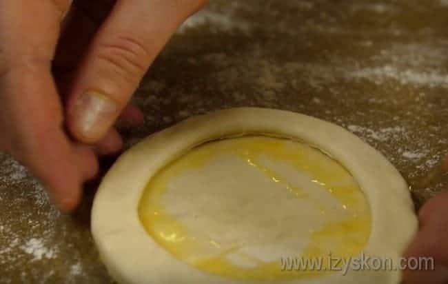 Получившийся бублик аккуратно накладываем на смазанную яйцом первую заготовку.