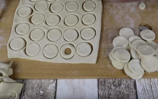Из слоеного теста вырезаем кружочки, а затем из половины кружочков делаем бублики.