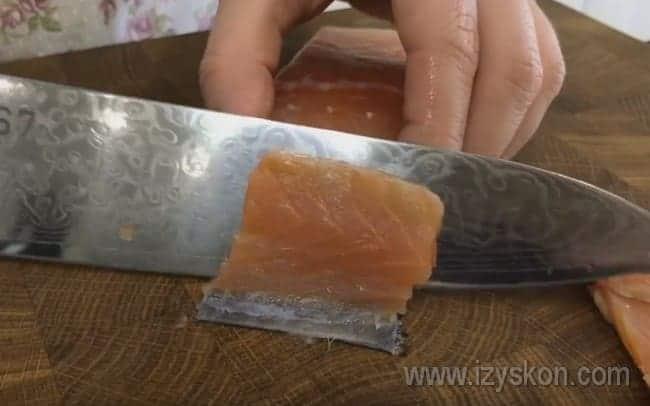 Тонкими кусочками режем красную рыбу.