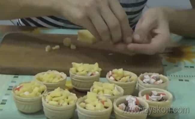На крабовые палочки раскладываем кусочки твердого сыра.