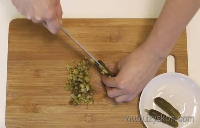 Нарезаем соленые огурцы мелким кубиком.