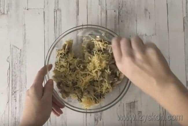 К остывшим грибам добавляем натертый на терке сыр.