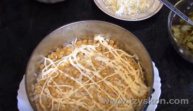Выкладываем и разравниваем по салату половину кукурузы.