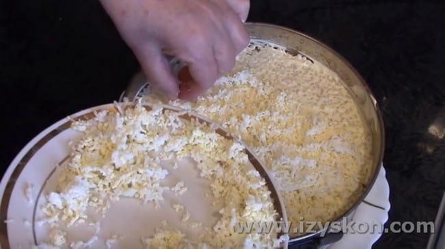 Далее посыпаем салат тертыми яйцами.