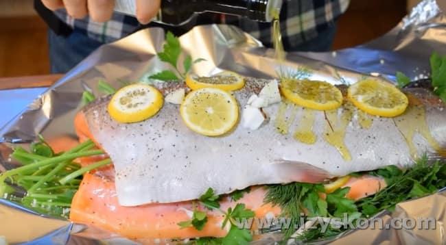 Поверх рыбины тоже кладем зелень, лимон, солим и перчим ее.