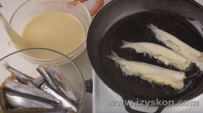 Каждую рыбку обмакиваем в кляр и выкладываем жариться на сковороду.