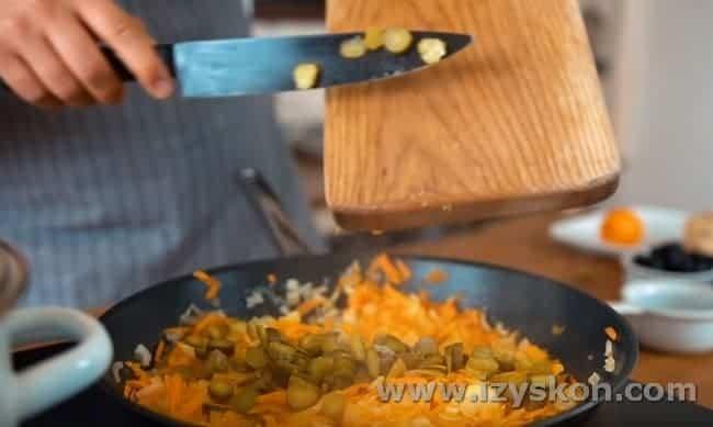 Выкладываем в сковороду нарезанные кружочками соленые огурцы.