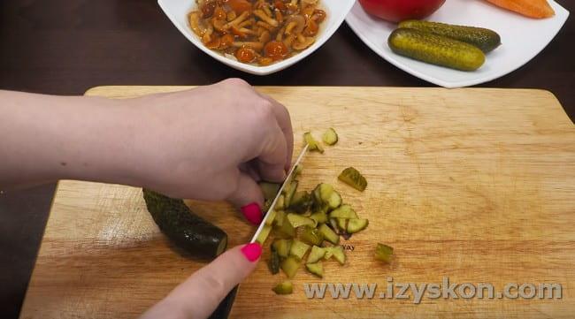 Нарезаем соленые огурцы.